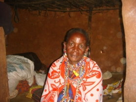 Maasai woman in her manyatta home, in Kajiado district, Kenya